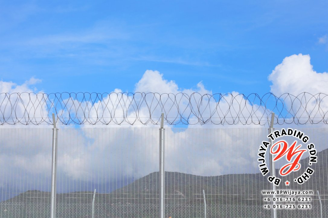 20279968 - chain link fence with barbed wire under blue sky